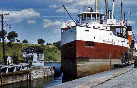 Westbound ship entering Lock 21.  The brow of the high embankment in the background is now just below the surface of Lake St. Lawrence at the western end of McDonald Island in the Long Sault Parkway.